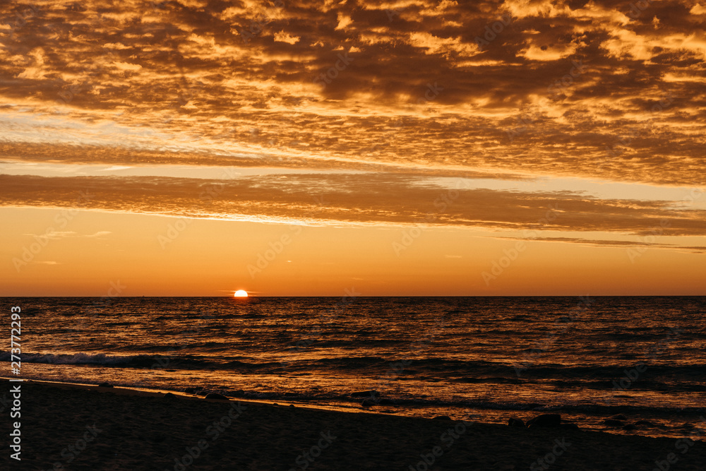 Beautiful sunset over the Baltic Sea shoreline. Jelenia Gora, Poland. Clouds lighten up from below.