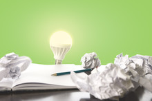 Ideas / Trial And Error Concept Image With Scrunched Paper, Pencil And Light Bulb Lighting Up.