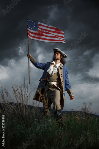 Fotomural  American revolution war soldier with flag of colonies over dramatic landscape