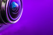 canvas print picture - Camera lens and dark purple backlight. Side view of the lens of camera on purple background. Camera Lens Close Up. Optics