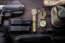 Military Tactical Equipment For The Departure. Assortment Of Survival Hiking Gear On Wooden Background. Top View - Vintage Film Grain Filter Effect Styles