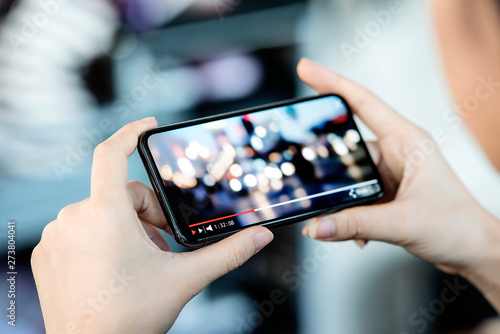 Foto  Cropped image of female hand holding smartphone and watching video while standing outdoor