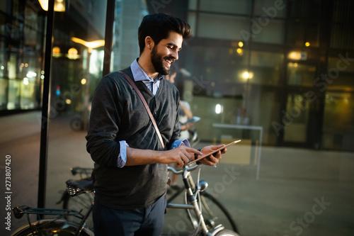 fototapeta na szkło Portrait of young businessman holding tablet outdoor