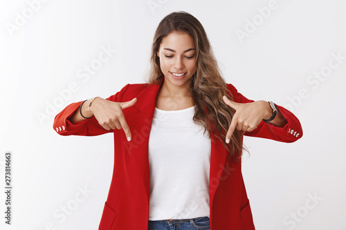 Valokuva  Curious good-looking young modern businesswoman wearing red trendy jacket pointi