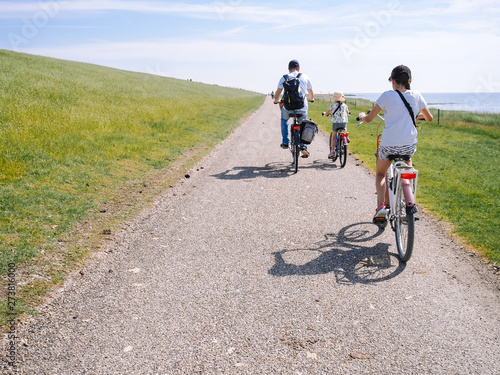 Fototapeta  Back view cyclists family traveling on the road in the dune area of Schiermonnikoog island