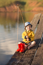A Little Boy Fishing And Wants To Catch The Biggest Fish. Little Boy Siting On Wooden Dock And Fishing At Sunset.