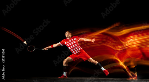 Obrazy Badminton   obraz-na-plotnie-young-man-playing-badminton-isolated-on-black-background-in-mixed-light-male-model-with-the-racket-in-action-motion-in-game-with-the-fire-shadows-concept-of-sport-movement-healthy-lifestyle