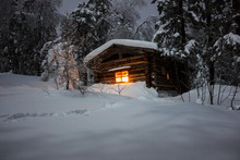 The Light Of A Christmas Candle In The Window Of A Lonely Wooden Log Hut In A Night Winter Dense Forest Under White Fluffy Snow