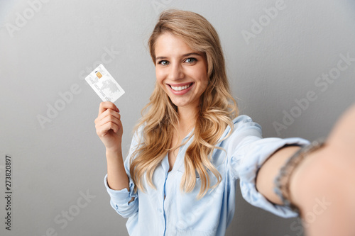 Obraz Photo of lovely blond businesswoman smiling and holding credit card while taking selfie - fototapety do salonu