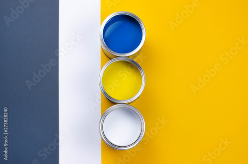 Three cans of multicolored paint on a gray-orange with a white background Canvas Print