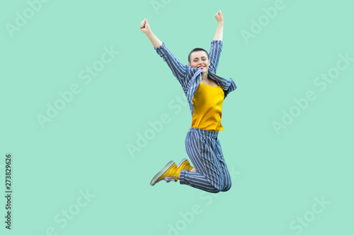 Fotografie, Obraz  Portrait of successful beautiful short hair young stylish woman in casual striped suit jumping and celebraiting her victory, looking at camera