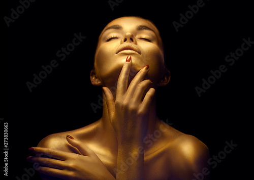 Fototapeta Beauty sexy woman with golden skin. Fashion art portrait closeup. Model girl with shiny golden professional makeup. Gold jewellery obraz