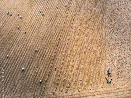 Nature and landscape, aerial view of fields with tractor with round baler and tractor with a rake, machines for collecting and pressing hay Wallpaper Mural