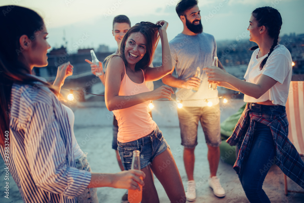 Fototapeta Friends having party on top of the roof. Fun, summer, city lifestyle and friendship concept