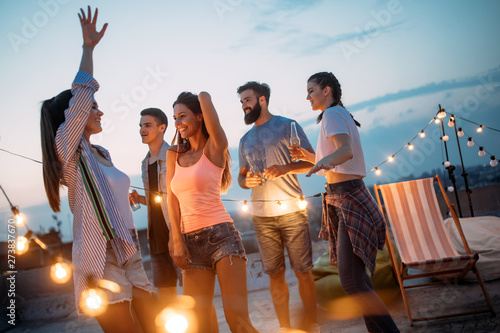 Obraz Happy friends with drinks toasting at rooftop party at night - fototapety do salonu