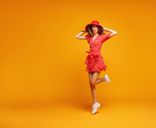 Concept Happy Emotional Young Woman In Red Summer Dress And Hat Jumping   On Yellow Background.