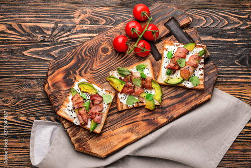 Платно Tasty toasts with bacon on wooden table