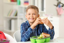 Little Schoolboy Eating Tasty Lunch In Classroom