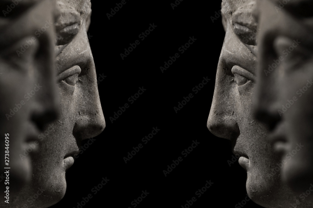 Fototapeta Symmetrical banner of marble ancient woman heads watching each other and arguing, talking at black background