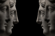 Symmetrical Banner Of Marble Ancient Woman Heads Watching Each Other And Arguing, Talking At Black Background