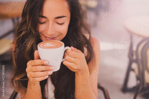 Young beautiful happy woman enjoying cappuccino in a cafe
