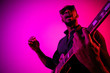 canvas print picture Young african-american musician playing the guitar like a rockstar on gradient purple-pink background in neon light. Concept of music, hobby. Joyful attractive guy improvising. Colorful portrait.