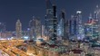 Aerial view of illuminated skyscrapers and road junction in Dubai night timelapse. Traffic on intersection in downtown with modern towers around. Cloudy sky