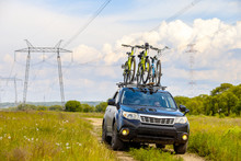 Black Crossover With Three Bicycles On Roof Rack