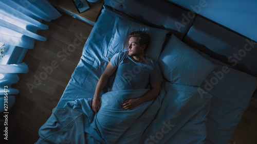 Top View of Handsome Young Man Sleeping Cozily on a Bed in His Bedroom at Night Wallpaper Mural