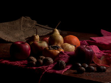Still Life Of Winter Fruits On Wooden Table And Purple Cloth