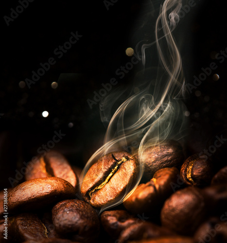 Foto op Aluminium Cafe Roasted coffee beans. Seeds of freshly roasted coffee with smoke. Coffee beans closeup with emphasis on the grain with smoke.