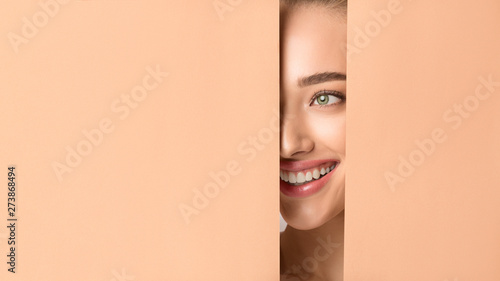 Photo Woman With Nude Makeup Peering Into Hole In Peach Paper