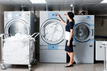 Cheerful Maid Touching Button On Washing Machine In Laundry