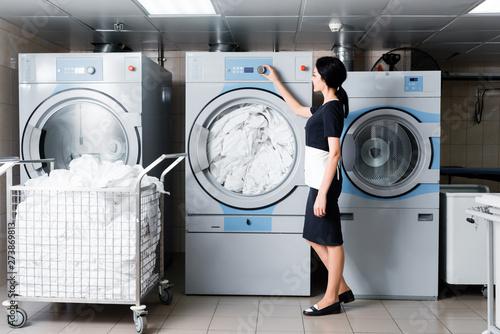 Obraz na płótnie cheerful maid touching button on washing machine in laundry