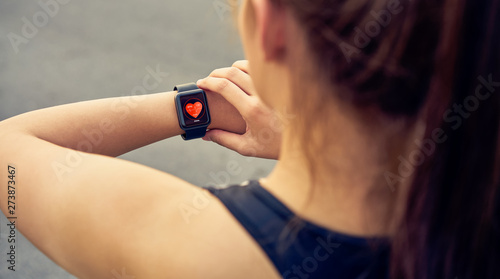 Valokuva  Young woman checking the sports watch measuring heart rate and performance after running