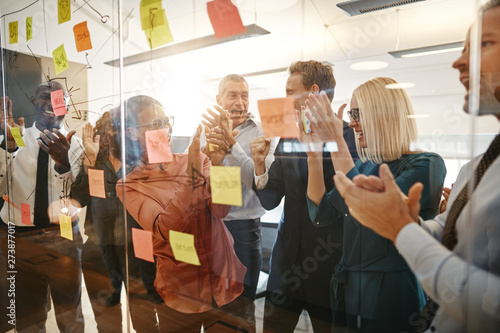 Tuinposter Laughing businesspeople clapping after an office brainstorming s