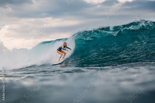 Surf girl on surfboard. Surfer woman and big blue wave Fotobehang