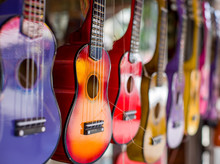 Multi-colored Guitars. Little Guitars Of Different Colors. The Picture Was Taken On The Open Aperture. One Guitar In Focus The Rest Is Blurred.