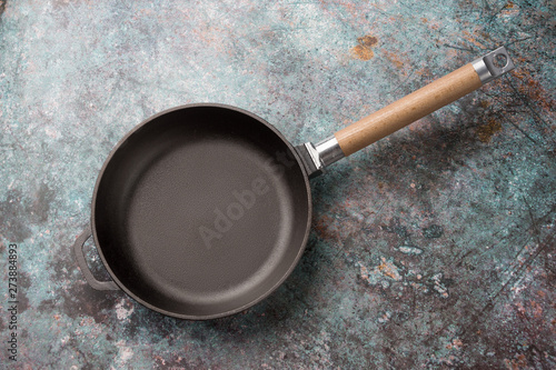Fototapeta Empty cast iron frying pan on dark green culinary background, view from above obraz