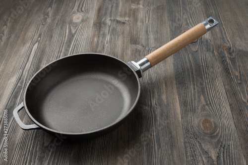 Cast iron pan on rustic wooden  background close up Fototapete