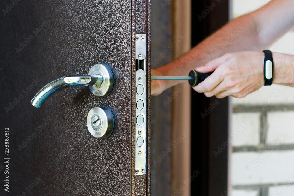 Fototapety, obrazy: Handyman repair the door lock in metal entrance door, Man fixing lock with screwdriver, Close-up of repairing door, professional locksmith installing new deadbolt lock on house