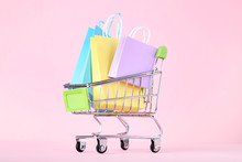 Small Metal Cart With Shopping Bags On Pink Background