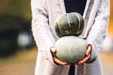 Hands Of Woman Holding A Green Pumpkins