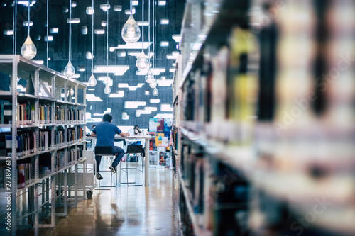Photographie People studying in public modern library - man sitting viewed from back working