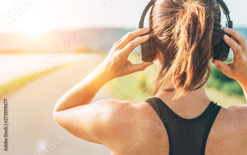 Close up image of teenager adjusting  wireless headphones before starting jogging and listening to music - 273898677