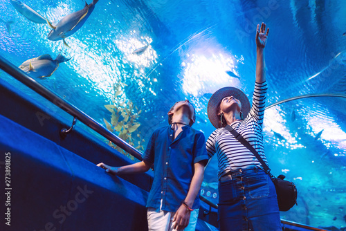 Son with his Mother watching underwater sea inhabitants in huge aquarium tunnel, Wallpaper Mural