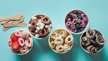Rolled Ice Creams In Cone Cups On Blue Background. Different Iced Rolls Top View Or Flat Lay. Thai Style Rolled Ice Cream