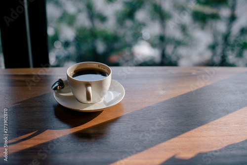 Foto  coffee cup on the table with sun light,vintage color tone.