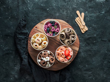 Rolled Ice Cream In Cone Cups On Rustic Round Wooden Tray On Dark Background. Different Iced Rolls Top View Or Flat Lay. Thai Style Rolled Ice Cream