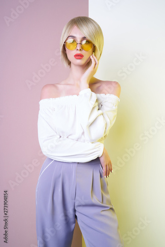 Fotobehang womenART Sensual stylish woman in blue pants. Blue-eyed lady with perfect lips in modern colour sunglasses
